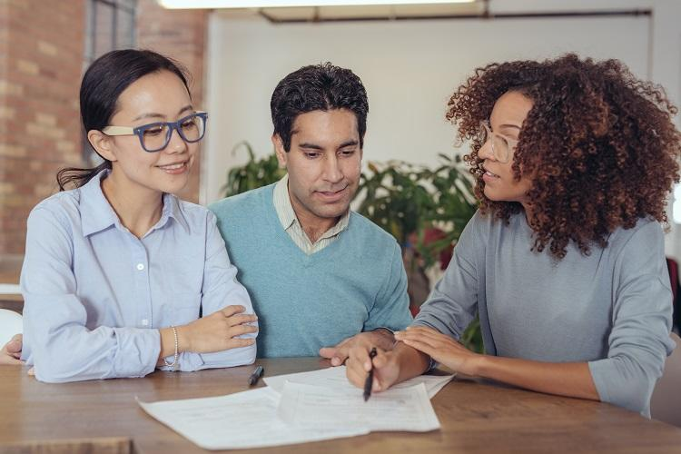 A bank manager meets with a couple to discuss their mortgage