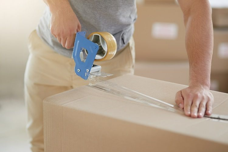 a man boxing up his belongings in preparation for moving house