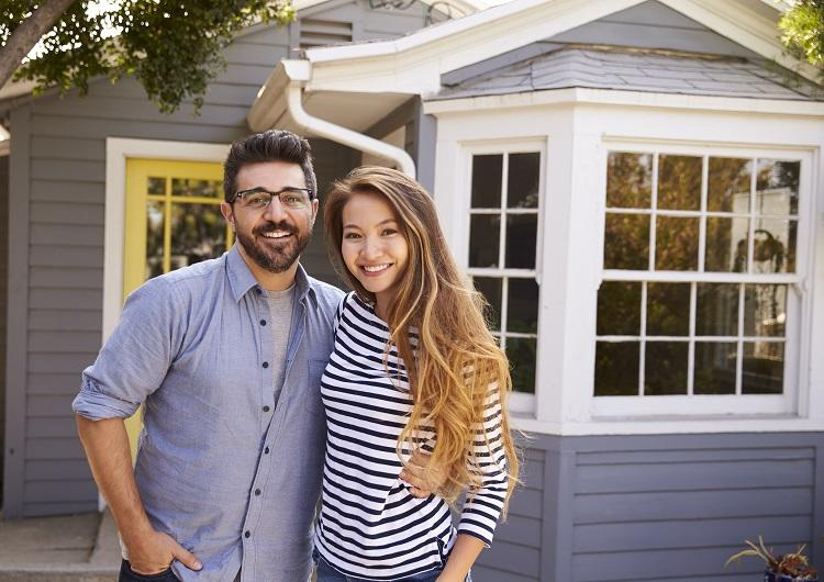 A couple stands in front of the home they've put a deposit on