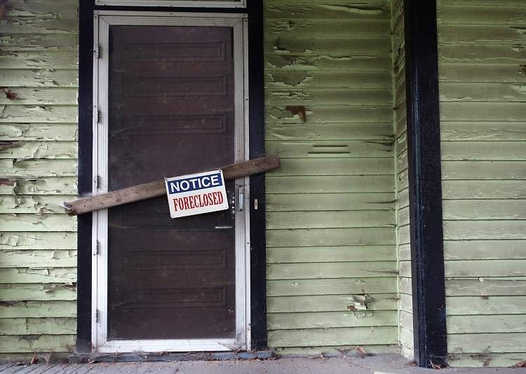 A decrepit house door with a foreclosed sign on it