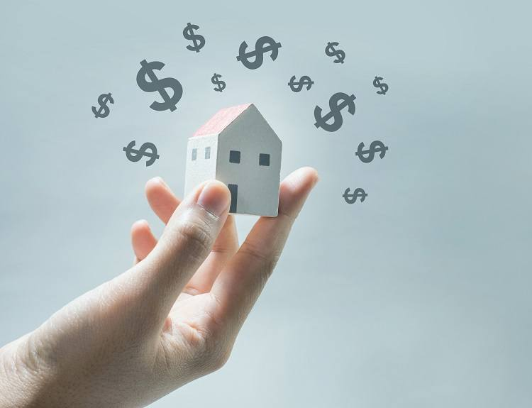 A human hand holds a model of a house surrounded by dollar signs