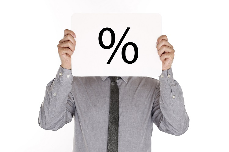 A man holds a piece of paper with a fixed interest percentage sign