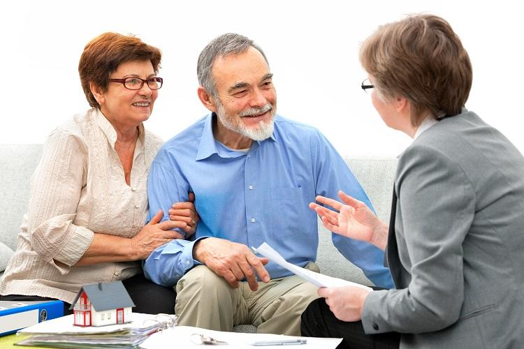 An older couple talk to a real estate agent