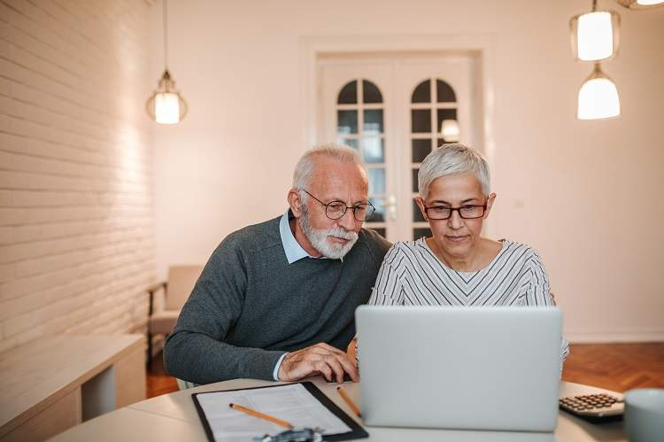 An older couple apply online for a mortgage
