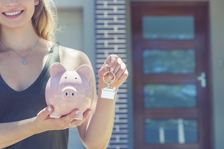 A woman holding a house key and piggy bank in front of a house