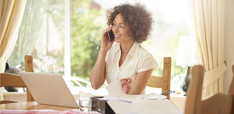 A woman on the phone with her lender about refinancing