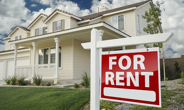 a For Rent sign in front of a rental investment property
