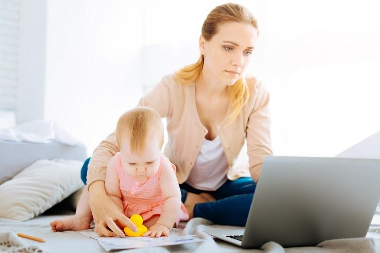 A young mother looks at mortgages with her child
