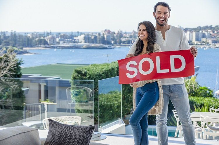 A young foreign couple stand inside their newly-bought Australian home with a sold sign