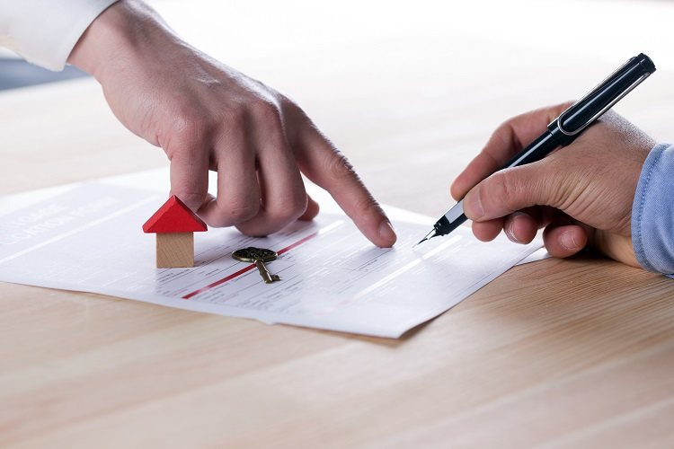 A new homeowner goes over the conditions of his mortgage as he signs paperwork