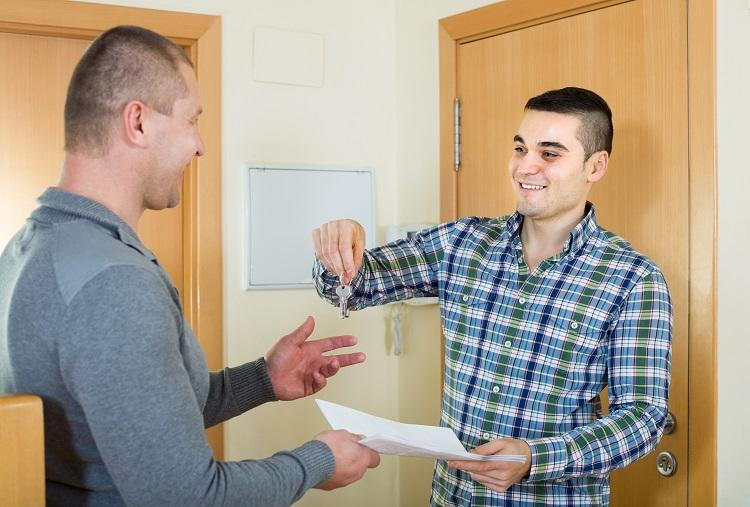A landlord hands over the keys to an apartment to his tenant