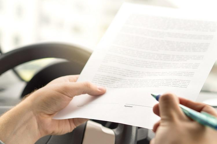 A man looks over a loan contract in his car