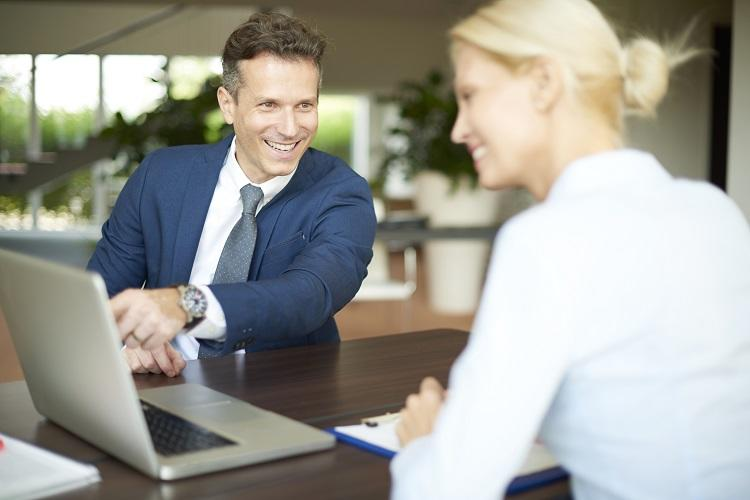 A mortgage broker assists a client on a laptop