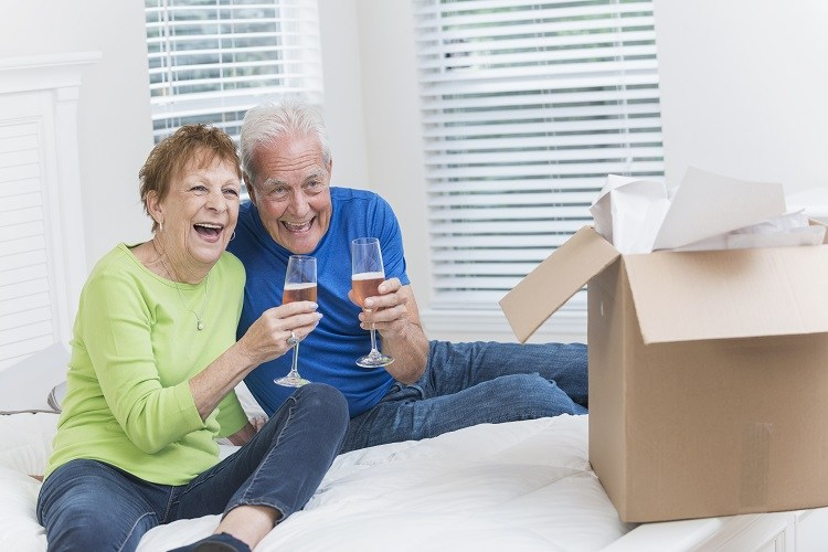 A senior couple celebrate downsizing to a new home with champagne