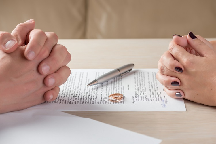 A wife and husband sign divorce documents