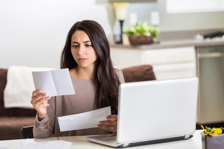 A woman looks at her credit card debt and her loan application
