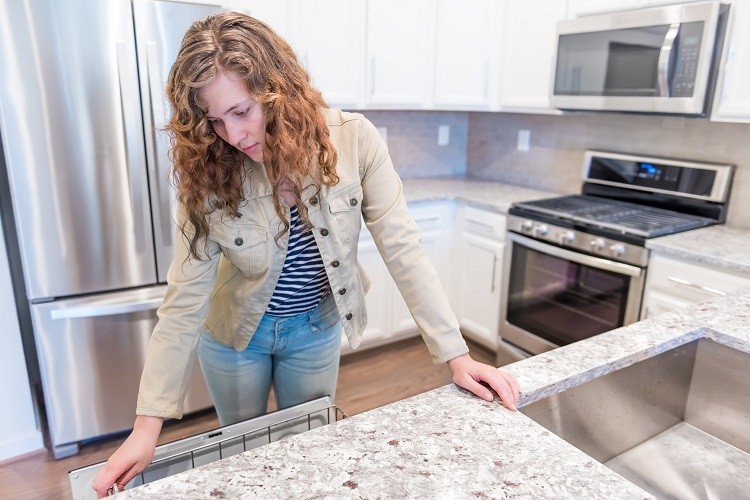 A young woman inspects a home's kitchen as part of a property inspection